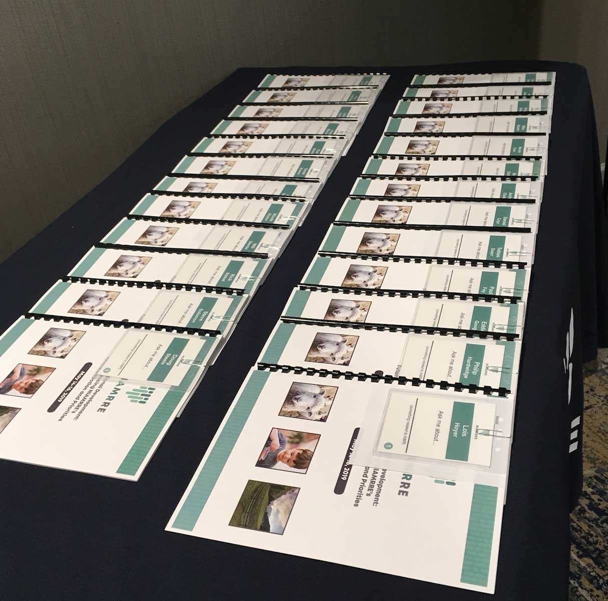Table displaying teal and white notebooks for NIAMRRE May foundational development meeting in Ames, Iowa